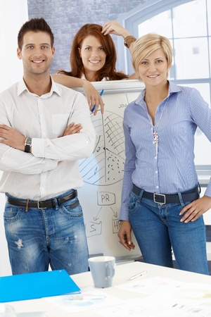 Portrait of happy businessteam standing at whiteboard in meeting room, smiling at camera. Stock Photo - 12472149
