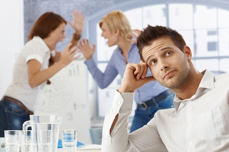 arguement: Portrait of upset businessman at meeting, businesswomen fighting in background. Stock Photo