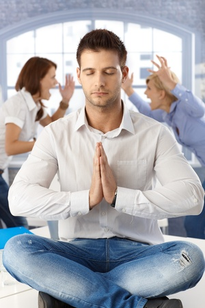 Businessman meditating at office with eyes closed sitting on desk, coworkers arguing in background.