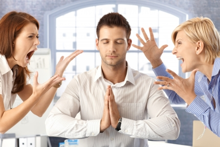 Meditating closed eye businessman in office with arguing colleagues shouting and fighting.