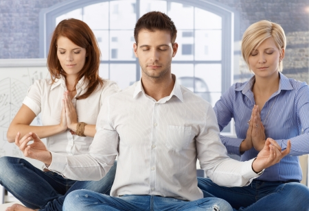 Coworkers meditating at office, taking break with their eyes closed. photo