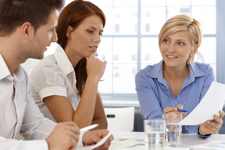 teamworking: Business team in discussion of work document, working together in office.