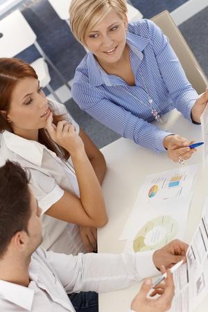 revisando documentos: Equipo de negocios en la reunión, la revisión de documentos, gráficos, diagramas, vista elevada. Foto de archivo