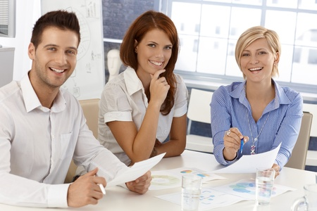 Happy businessteam at meeting, working with documents, laughing, looking at camera. Stock Photo - 12471908