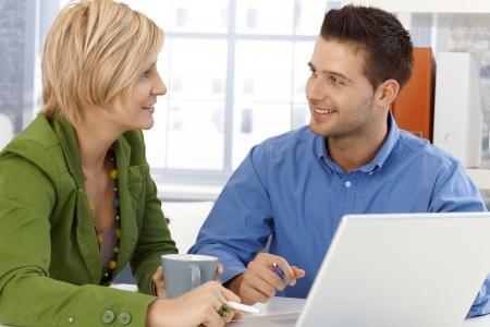 dos personas hablando: Colegas en el chat, sentados juntos en la mesa de la oficina, sonriendo.