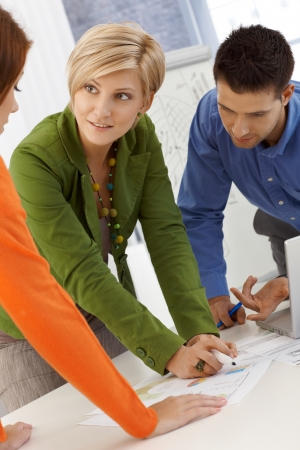 casual meeting: Smiling coworkers brainstorming, using notes, working together, standing at meeting table. Stock Photo