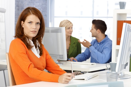 Portrait of office worker woman sitting at desk, looking at camera, colleagues at background. photo