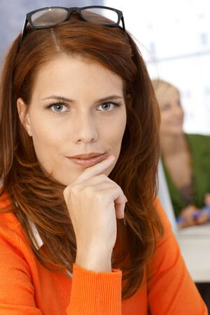 beautiful redhead: Closeup portrait of pretty office worker woman smiling at camera confidently. Stock Photo