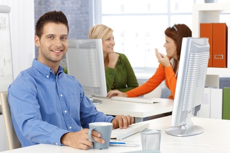 desktop computers: Casual happy businessman with sitting at desk in office, smiling at camera, with colleagues in background.