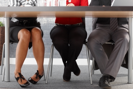man legs: Legs of businesspeople at meeting, sitting together at meeting table in office.
