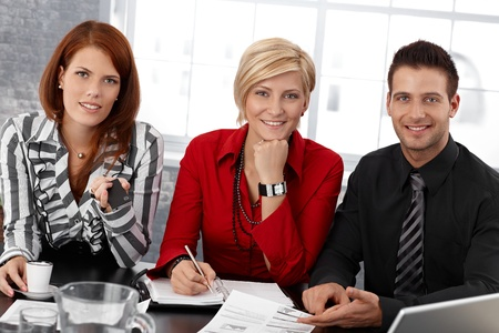 Portrait of smiling confident smart businesspeople at meeting, smiling at camera. photo