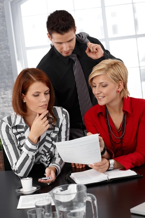 Businessteam busy working, discussing document at meeting table. Stock Photo - 12471918