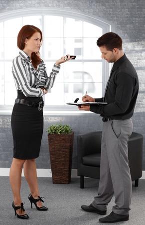 dictating: Empresaria que dicta a la secretaria, de pie en la oficina, asistente de tomar notas. Foto de archivo