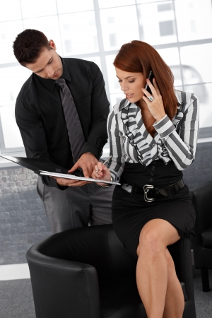 Businesswoman signing document, busy speaking on mobile phone, assistant helping. photo