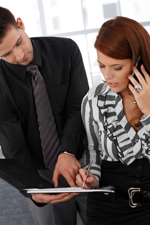 Assistant holding contract for busy elegant businesswoman to sign. photo