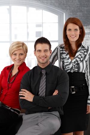 vertical image: Portrait of confident elegant businessteam smiling at camera.