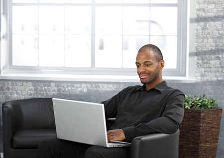 Businessman working on laptop computer, sitting in armchair in office lobby. photo
