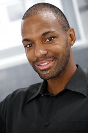 black americans: Closeup portrait of smiling goodlooking black man looking at camera.