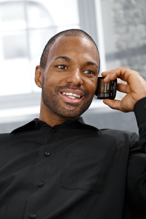 Cheerful ethnic man speaking on mobile phone, smiling. photo