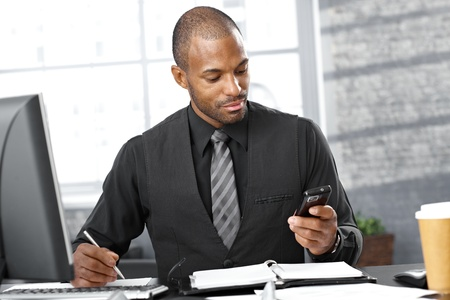 taking note: Ritratto di uomo d'affari astuto impegnato alla scrivania, usando il telefono cellulare, prendere appunti, di concentrazione.