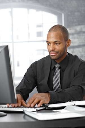 Elegant afro businessman concentrating on working on computer at office desk. photo
