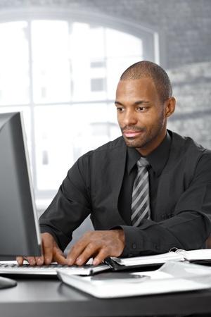 black businessman: Elegant afro businessman concentrating on working on computer at office desk.