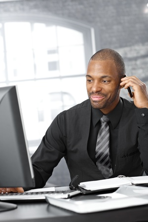 Businessman multitasking, working with computer and having mobile phone call, smiling. photo