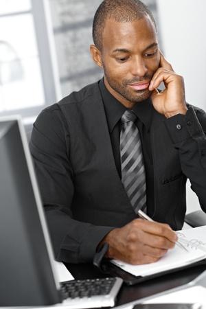 persona escribiendo: Inteligente hombre de negocios afro escribir notas en organizador personal, pensando.