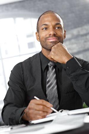 taking note: Pensiero intelligente uomo d'affari afro, prendere appunti, sorridendo. Archivio Fotografico