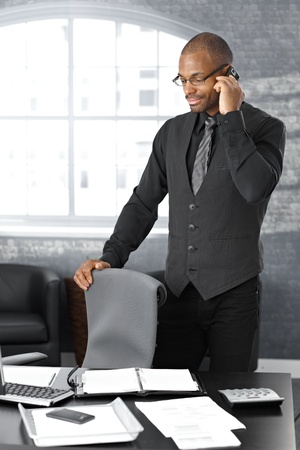 Businessman on mobile telephone call, standing at office desk, concentrating. photo