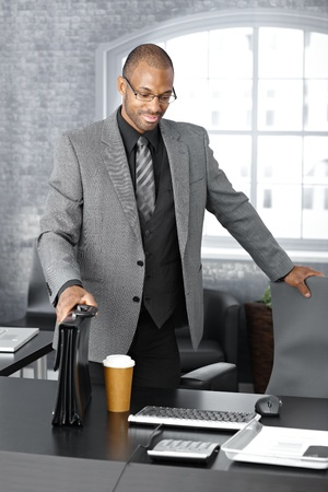 Elegant afro businessman arriving to office with coffee and briefcase, smiling. photo