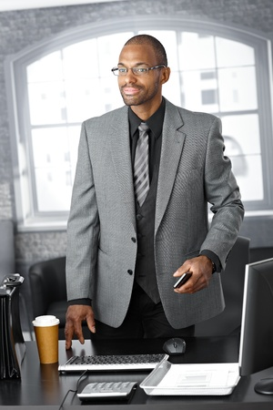 Elegant businessman standing at office desk with mobile phone handheld, briefcase and coffee on table. photo
