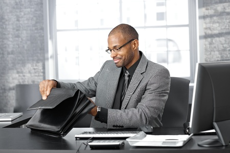 Businessman sitting at office desk searching in briefcase. Stock Photo - 12472060