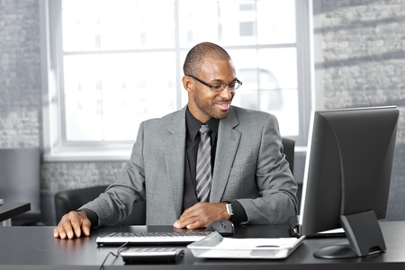 Portrait of happy smart black businessman sitting at desk in office, smiling. Stock Photo - 12471919