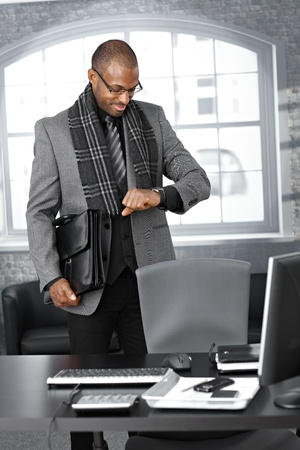 leave: Smiling businessman checking time on watch at office, standing by desk with briefcase ready to leave. Stock Photo