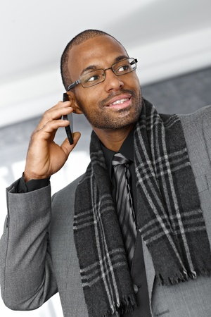 Smart ethnic businessman speaking on mobile phone. Stock Photo - 12472162
