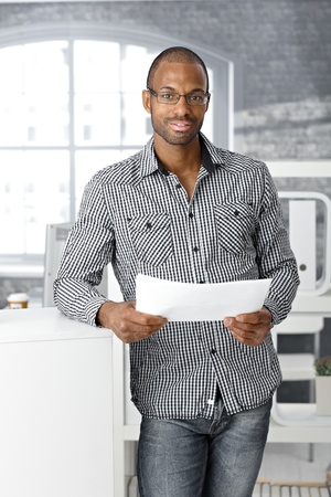 Portrait of ethnic office worker smiling, standing with document handheld, looking at camera. photo