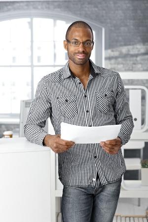 revisando documentos: Retrato de oficinista étnica sonriente, de pie, con mano de documentos, mirando a la cámara.