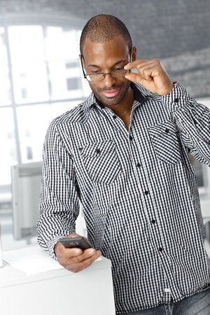 Afro-American office worker man using mobile phone at work. photo