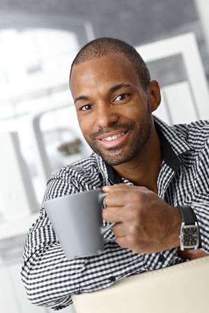 Portrait of happy goodlooking afro office worker guy on coffee break. photo