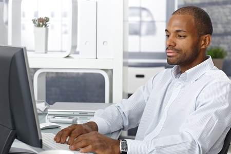 man using computer: Casual afro businessman sitting at office desk, working on desktop computer.
