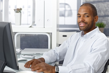 Businessman working on computer at office desk, looking at camera, smiling. Stock Photo - 12471730