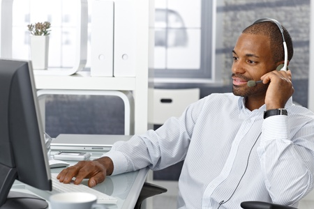 headset business: Callcenter agent sitting at office desk, working on phone with headset. Stock Photo