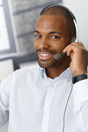 casual clothing: Closeup portrait of smiling handsome Afro-American customer service representative working with headset. Stock Photo