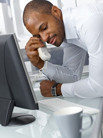 Handsome afro businessman concentrating on landline phone call, leaning on office desk. photo