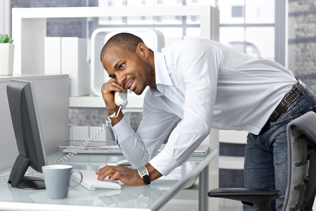 Casual happy businessman talking on landline phone in office, standing leaning on desk. photo