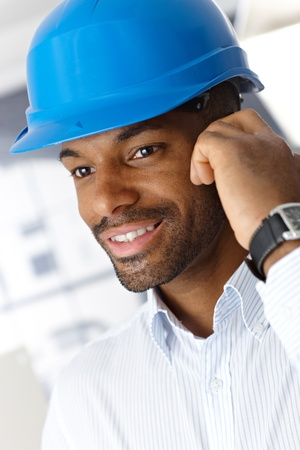 Closeup portrait of smiling ethnic engineer in hardhat on phone call. photo