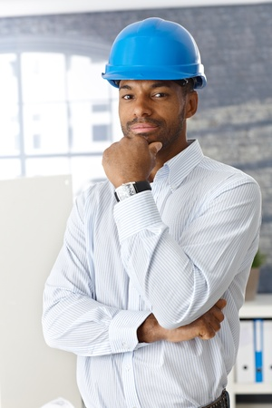 Architect in hardhat standing in office thinking, looking at camera. photo