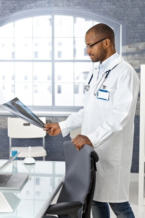 Ethnic doctor examining x-ray image, standing by medical office desk. photo