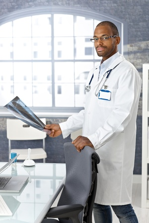 Young afro doctor standing at desk with xray image handheld, looking at camera. Stock Photo - 12471700
